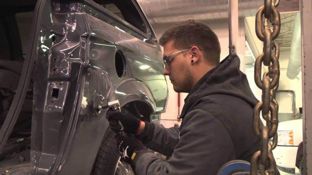 Auto body repairman using die grinder