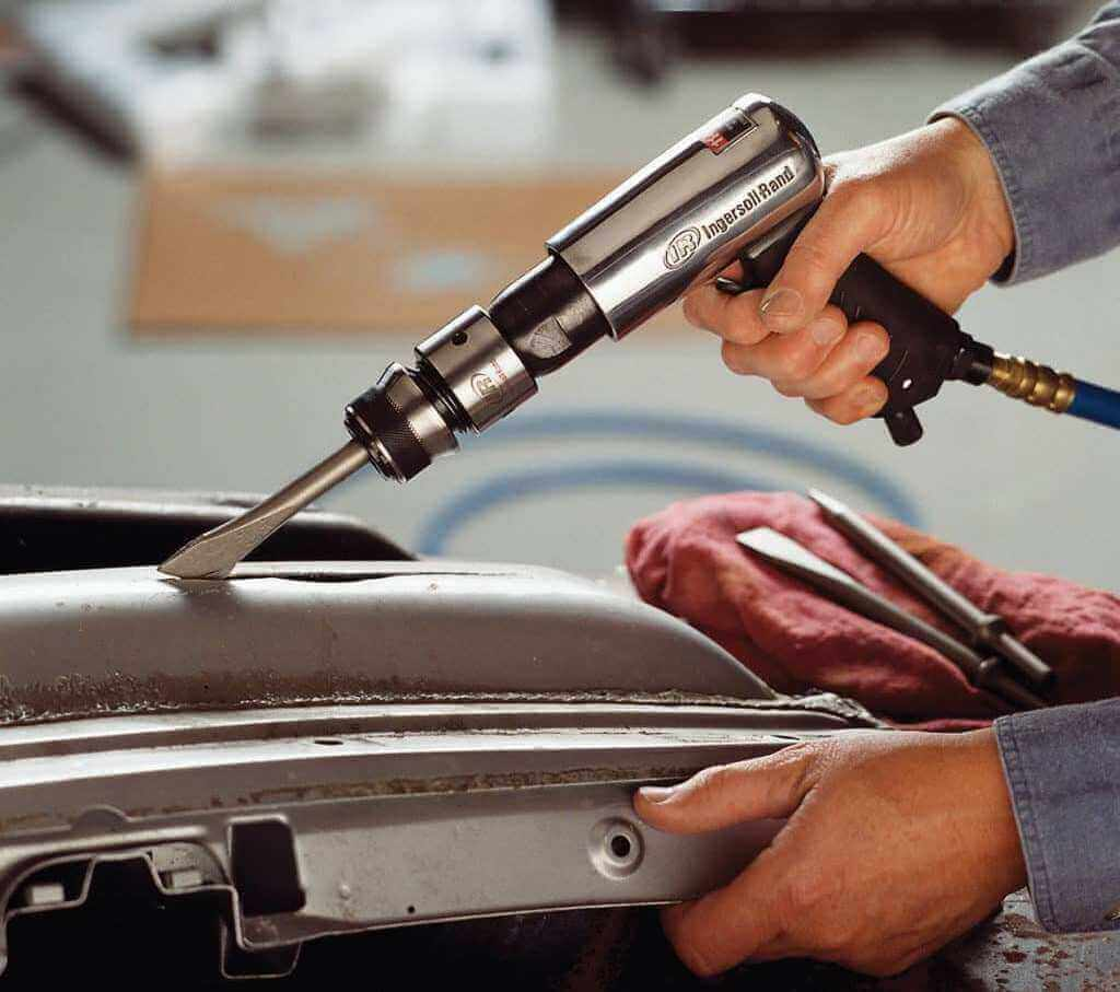 Auto mechanic using air hammer