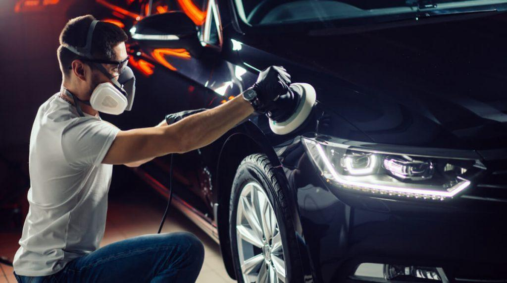man waxing a car with dual-action polisher