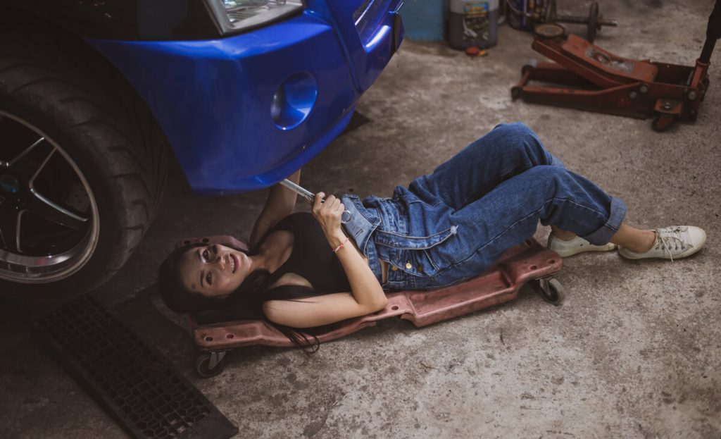 Woman working under a car with a creeper